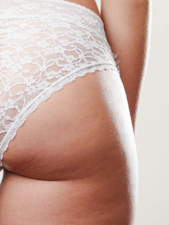 absence: Absence of cellulite. Part body of slim fit girl bottom buttocks. Woman wearing white lacy lingerie. Diet aspects.