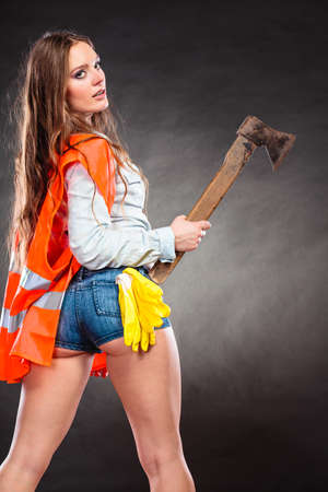 axe girl: Sexy alluring woman wearing helmet and safety workwear holding axe chopper. Strong girl feminist working in man profession. Independent female. Stock Photo