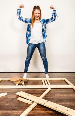 Feliz sonriente mujer fuerte mostrando los músculos que se divierten montaje de muebles de madera. aficionado al bricolaje. Niña haciendo mejoras para el hogar.