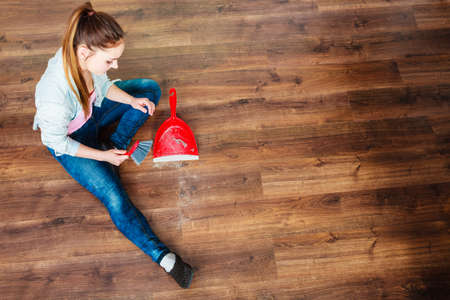 unusual angle: Cleanup housework concept. cleaning woman sweeping wooden floor with red small whisk broom and dustpan unusual high angle view