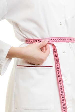 Slank dieetconcept. vrouw in witte laboratoriumjas. Dokter specialist diëtist meten van haar taille geïsoleerd.