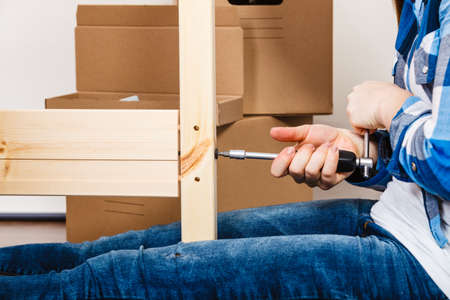 enthusiast: Human hand assembling wood furniture using screwdriver. DIY enthusiast. Home improvement.