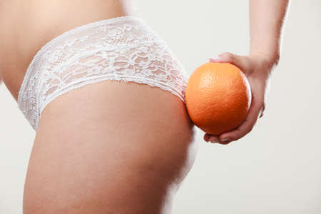 Absence of cellulite. Part body of slim fit girl holding orange next to the bottom buttocks. Woman wearing white lacy lingerie. Diet aspects. Stock Photo
