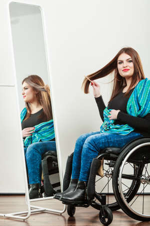 handicap people: Real people, disability and handicap concept. Teen girl handicapped woman sitting on wheelchair in front of mirror combing hair. Daily personal care