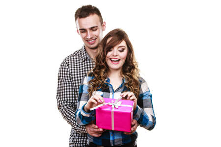 male bonding: Couple holidays and happiness concept. Smiling handsome man giving his woman pink gift box isolated on white