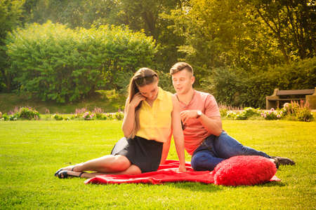 argument from love: Love and dating. Young fashionable couple lovers in park. Woman and man argument. Picnic concept.