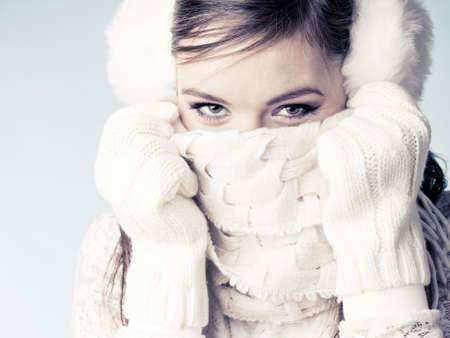 covering the face: Cute pretty woman in earmuffs covering face mouth with scarf. Happy lovely girl in studio.