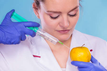 apple gmo: Scientist doctor injecting apple with syringe. Woman chemist holding genetically modified fruit. GM food modification.