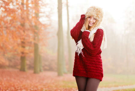 Portrait of pretty smiling fashionable woman in fall forest park. Happy gorgeous young girl in fur winter hat and sweater pullover. Autumn fashion.