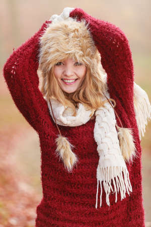 pullover: Portrait of pretty smiling fashionable woman in fall forest park. Happy gorgeous young girl in fur winter hat and sweater pullover. Autumn fashion.