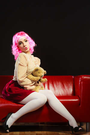 childlike: Mental disorder concept. Young childlike woman wearing like puppet doll sitting with teddy bear toy on red couch dark black background