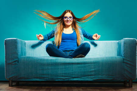 windblown: Fashion young woman in full length. Fashionable girl wearing denim sitting on couch wind in hair blue background Stock Photo