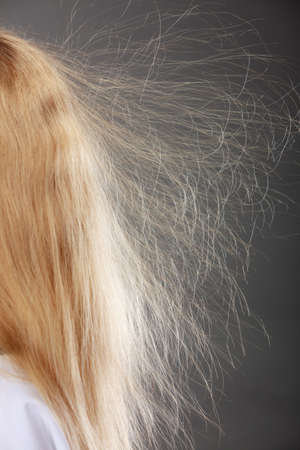 electrifying: Closeup of woman girl with static blonde long hair.