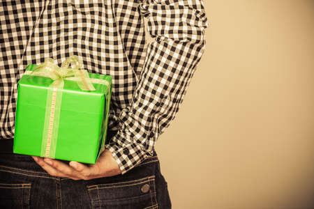 gift behind back: Man hiding green gift box with white ribbon behind back. Closeup of male hand holding christmas present. Guy wearing flannel shirt. Birthday, holiday surprise. Instagram filtered.