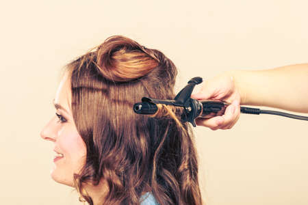 hair stylist: Stylist curling hair for young woman. Girl care about her hairstyle Stock Photo