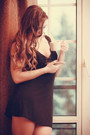 energizing: Sensual seductive woman in lingerie drinking cup of coffee by curtain and french door window at home. Young girl with hot energizing beverage stay awake. Caffeine energy.