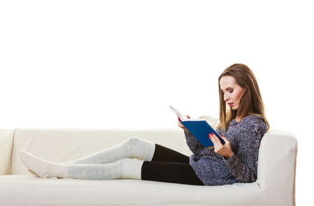 woman couch: Leisure, education, literature and home concept. Woman sitting on couch reading book at home