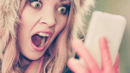 asustado: Retrato de mujer bonita miedo miedo a hablar en el tel�fono m�vil. Chica joven magn�fica en sombrero de invierno de la piel y la chaqueta. La manera del oto�o y la comunicaci�n. Foto de archivo