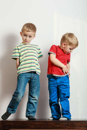 frendship: Free time, fun and independence. Little boys play together indoors fit new clothes. Blonde children wear colorful clothes.