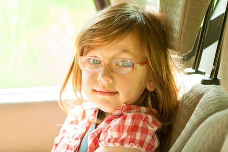seat belt: Little girl child kid in glasses with seat belt fastened sitting in car. Holidays vacation trip. Safe summer travel.