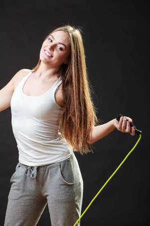 actively: Young fit slim woman spend actively free time. Beauty happy girl wearing sports clothes with jumping skipping rope on black background. Stock Photo