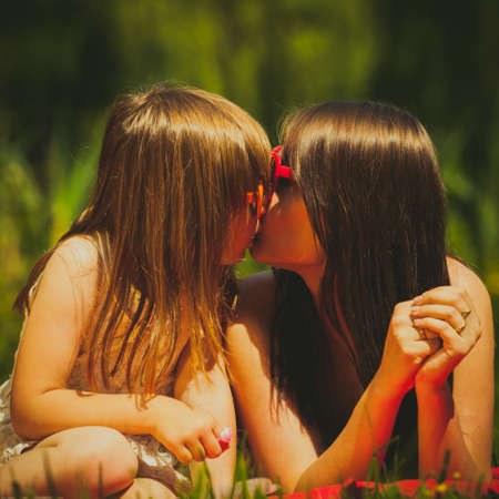 girls kissing girls: Mother parent and daughter child on picnic wearing heart shaped glasses. Summer vacation leisure. Happy family relaxing in park meadow. Stock Photo