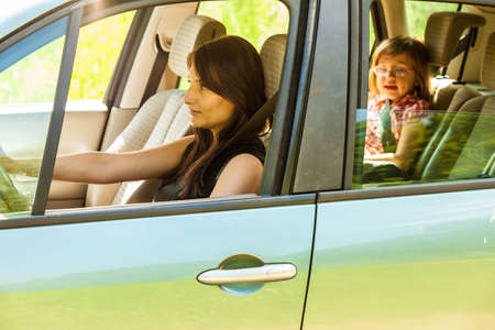 fastened: Mother and little girl child kid with seat belt fastened sitting in car. Holidays vacation trip. Safe summer travel. Stock Photo