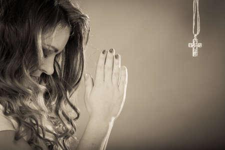 simbolo de la mujer: Mujer que ruega a Dios, Jesucristo, con el colgante de collar con una cruz. Religión fuerte fe cristiana. Cristianismo.