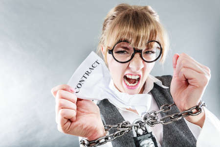 slave labor: Business and stress concept. Furious businesswoman in glasses with chained hands holding contract grunge background unusual angle view
