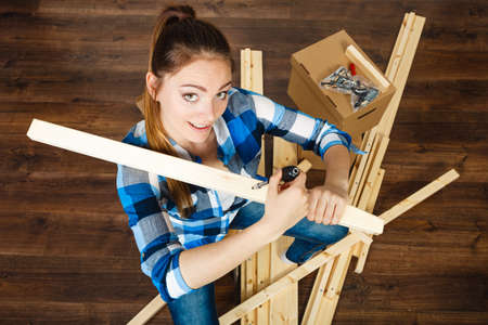 Woman moving into new apartment house assembling furniture with screwdriver. Young girl sitting on chair arranging interior and unpacking boxes. Top view.