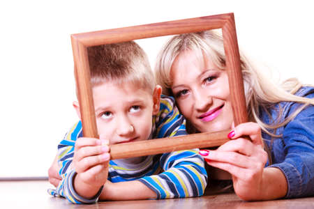 hand lay: Spending time family bonds parenthood. Mother and son have fun play with empty picture frame hold in hand lay on floor.