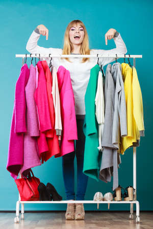 Happy smiling pretty woman pointing at clothes in wardrobe. Gorgeous young girl customer shopping in mall shop. Fashion clothing sale concept.