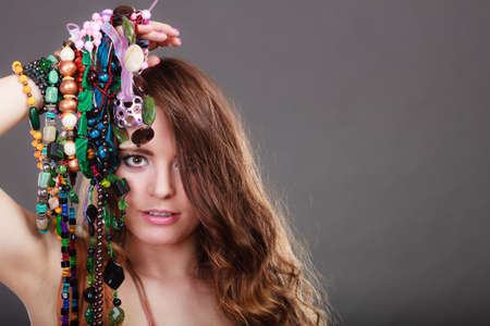 plentiful: Pretty young woman holding many plentiful of precious jewelry necklaces beads. Portrait of gorgeous fashion girl in studio on gray. Stock Photo