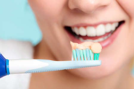 oral cavity: Pretty young girl with electric brush cleaning white teeth using toothpaste. Happy woman clean her oral cavity caring about dental health.