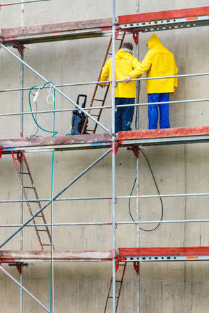 dirtiness: Men cleaning wall. Scaffolding, construction site in progress. Building renovation. Cleaning dirtiness.
