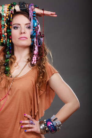 plentiful: Pretty young woman wearing bracelets holding many plentiful of precious jewelry necklaces beads. Gorgeous fashion girl.