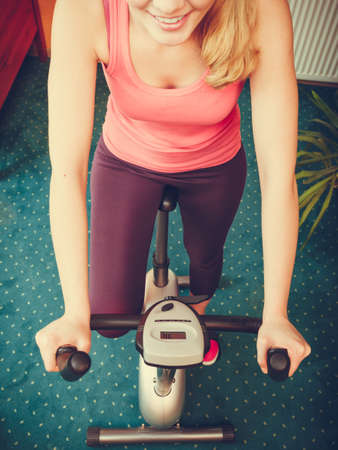 stationary bicycle: Active human working out on exercise bike stationary bicycle. Sporty person training at home. Fitness and weight loss concept. High angle view.