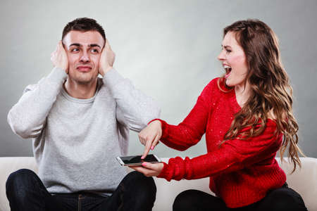 Angry furious wife shouting at husband showing text messages from lover mistress on his mobile phone. Outraged girlfriend find out about boyfriend affair romance betrayal. Cheating man covering ears.