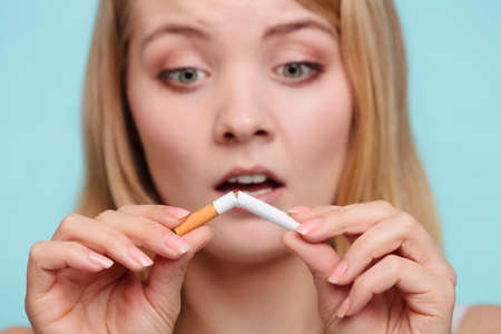 breaking up: Disappointed pretty girl at breaking up with cigarette. Addicted nicotine problems in young age. Quitting from addiction concept by sorrowful.