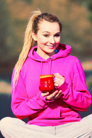 care about the health: Young pretty girl at park holding mug with hot tea. Woman care about health sitting on fresh air.