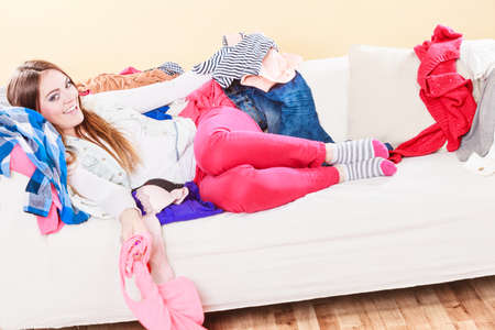 habitacion desordenada: Happy woman lying on sofa couch in messy living room. Young girl surrounded by many stack of clothes. Disorder and mess at home. Foto de archivo