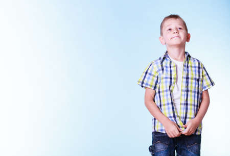undress: Fitting garment for kids independence. Boys stand alone fastening shirt. Prepare for adolescence trying new clothes.