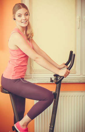 escucha activa: Active young woman working out on exercise bike stationary bicycle. Sporty girl training at home listening music. Fitness and weight loss concept. Foto de archivo