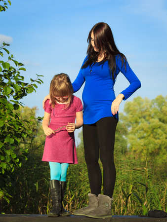 upbringing: Pregnancy, motherhood and children upbringing. pregnant woman outdoor in park with little girl. Mother and daughter having relationship difficulties