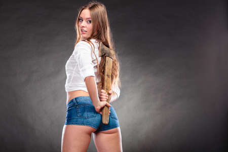 feminist: Sexy seductive woman holding axe chopper behind back. Strong girl feminist working in man profession. Independent female. Stock Photo