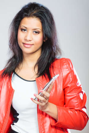mobile communication: Technology and communication concept. Young attractive fashionable woman in red jacket using her mobile phone.