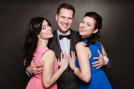 Triángulo de amor o amistad. Retrato de la sonrisa de dos mujeres y un hombre con ropa elegante en negro. Fiesta de lujo.