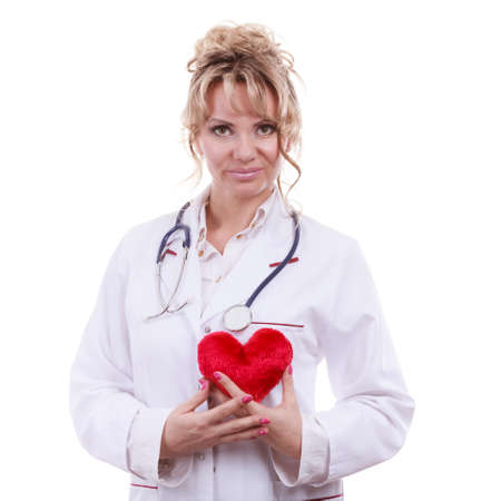 the cardiologist: Periodic examinations. Cardiology concept. Female cardiologist holding red heart. Middle aged doctor with stethoscope and white medical apron uniform. Isolated on white.