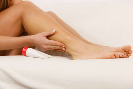 calf pain: Woman fit fitness girl putting ointment cream on injured calf. Health care crapm problem muscle pain in leg