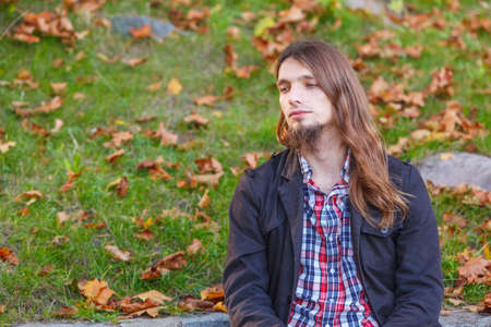 man long hair: Man long hair sad thoughtful sitting on bench outdoor in autumnal park Stock Photo